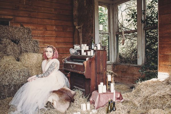woman sitting in barn with hay and piano