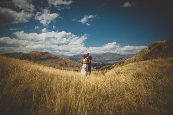 married couple standing in field surrounded by mountains